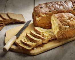 Gesneden brood en suikerbrood, gepresenteerd op een houten snijplank. Het mes ligt ernaast