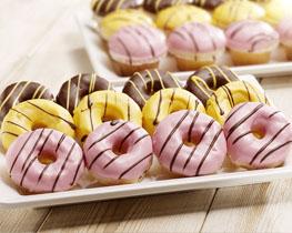 Donuts met gele, bruine en roze coating, gepresenteerd op een witte schotel